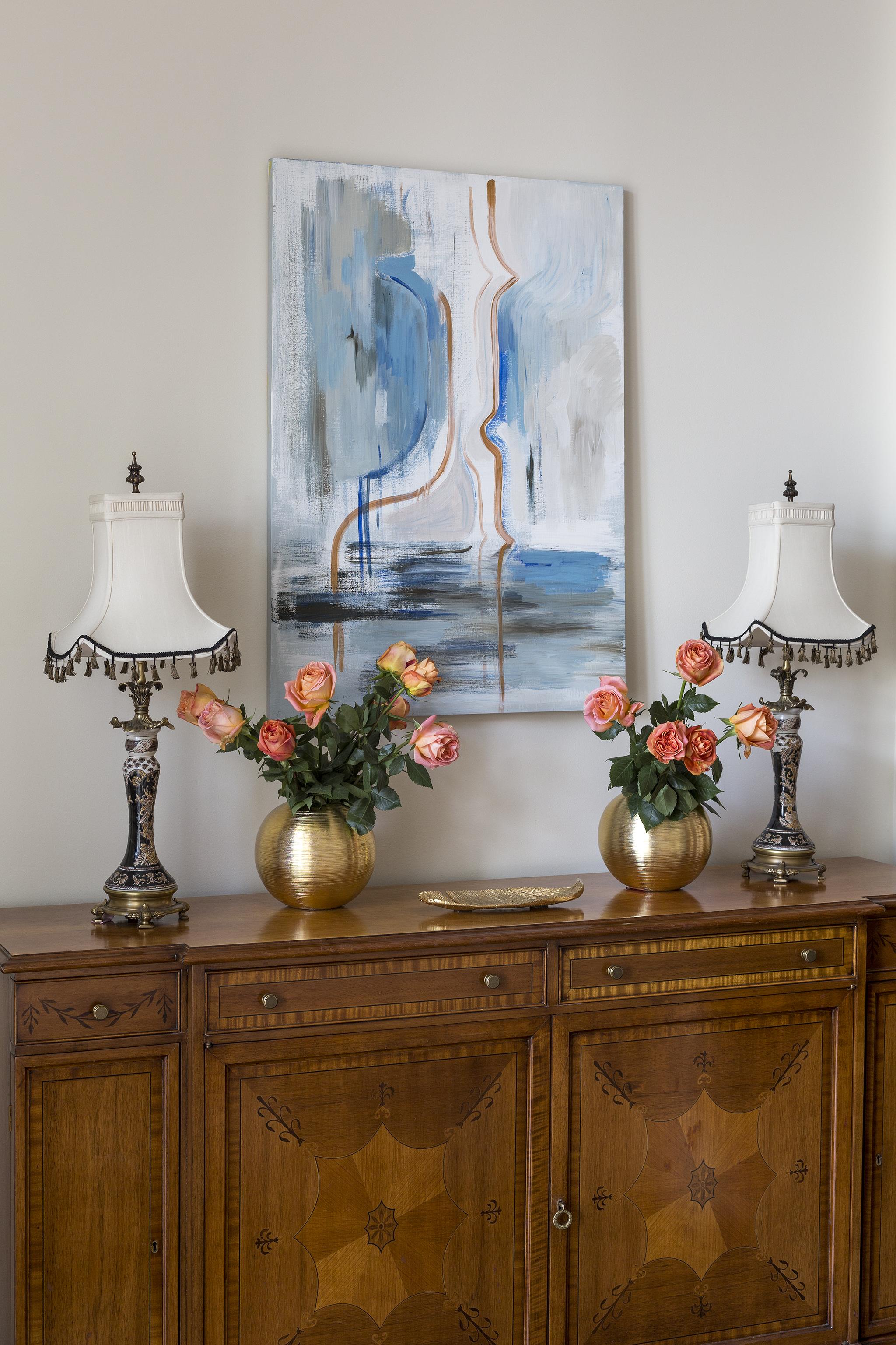 Чтобы слегка разбавить такую классическую атмосферу, над комодом поместили современное искусство крупного формата.