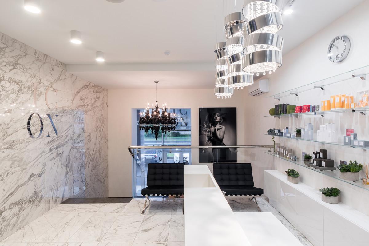 Витрины продаж в салоне всегда формируют компоновку  зоны рецепции. В этом салоне они выполнены из осветленного стекла и белого искусственного камня.