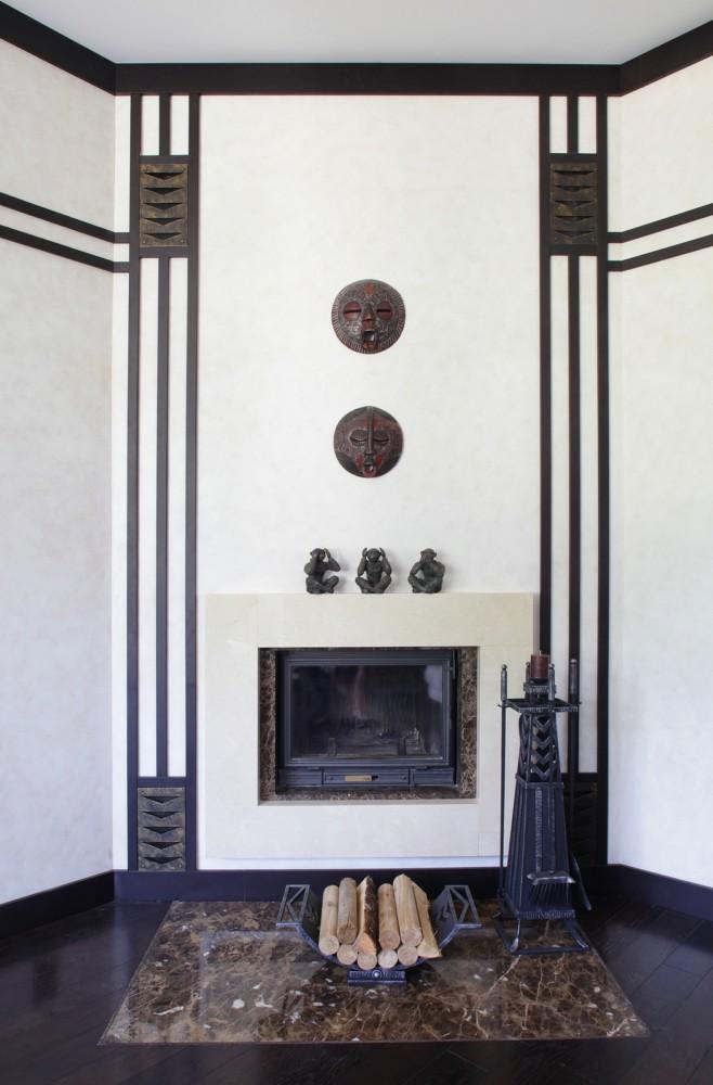 Стены гостиной отделаны светлым декоративным покрытием под камень. Они контрастируют с восточными масками и фигурками цвета венге, которые в свою очередь гармонично перекликаются с тёмными молдингами, оконными рамами, дверными карнизами и роскошным дубовым полом.